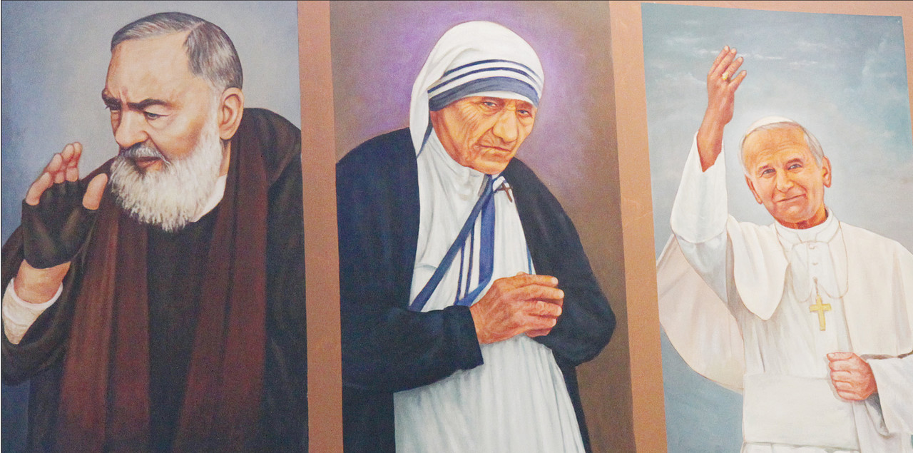 SAINTLY INSPIRATIONS: Saint Padre Pio, at left, Saint John Paul II, at right, and Blessed Teresa of Calcutta, center, whose cause for canonization was recently approved by the Vatican, is among the holy figures whose portraits now grace the walls of St. Patrick Church. Mohammed plans to adjust the caption above her portrait following her canonization.