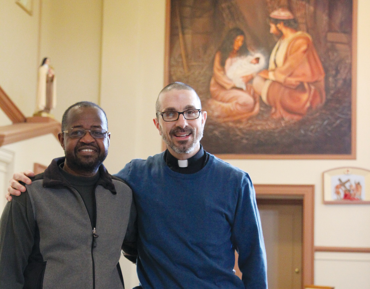 SOLIDARITY: From left to right, artist Munir Deishinni Mohammed and Father James Ruggieri hope their collaboration on the St. Patrick renovations will encourage other interfaith projects in the community. Both men named the nativity scene, pictured behind them, as their favorite painting in the collection.
