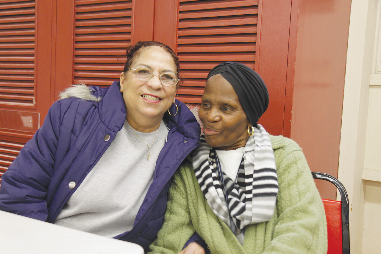 "FAMILY LIVING: Shirley Brame and Lorraine DeCosta share a laugh over lunch at the St. Martin de Porres Center. ""This is a friendly place. Everybody's treated like family here,"" said DeCosta."