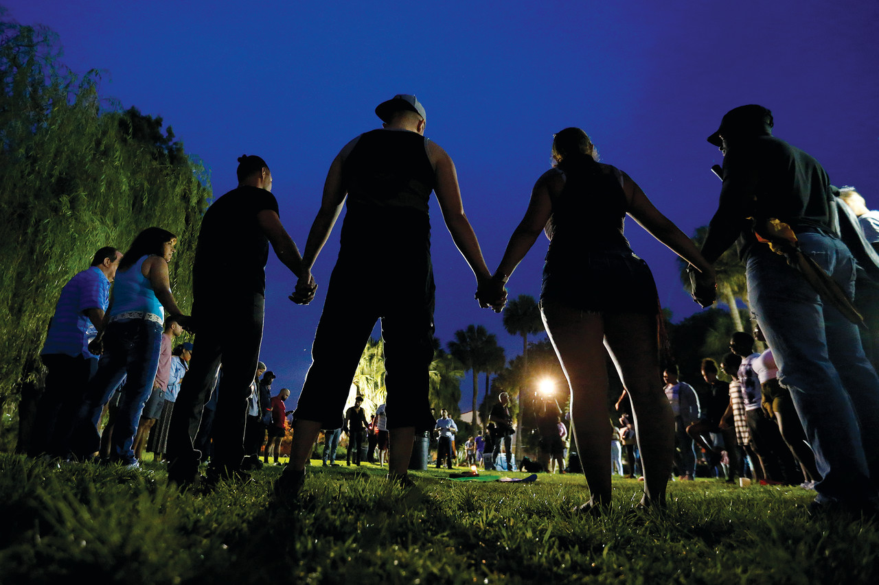 People hold hands in a circle during a June 12 vigil in an Orlando, Fla., park following a mass shooting at the Pulse gay nightclub in that city earlier that morning. (CNS photo/Carlo Allegri, Reuters) See ORLANDO-SHOOTING-TRAGEDY and POPE-ORLANDO June 13, 2016.
