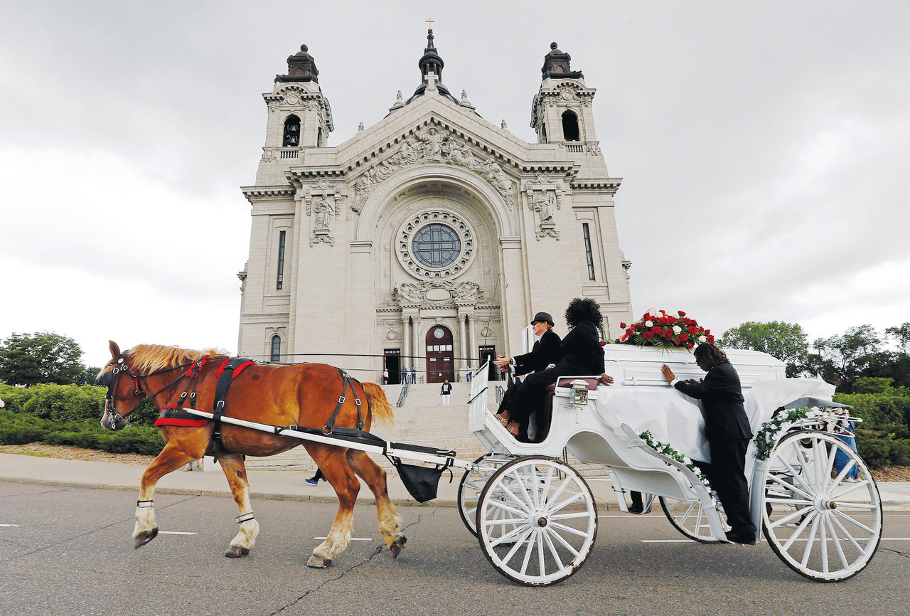 A horse-drawn carriage carries the casket of  Philando Castile July 14 as it passes the Cathedral of St. Paul in St. Paul, Minn. Church officials say the mother of 32-year-old man, who was not Catholic, requested the cathedral hold an ecumenical funeral service for her son. Castile was shot and killed by a police officer July 6.