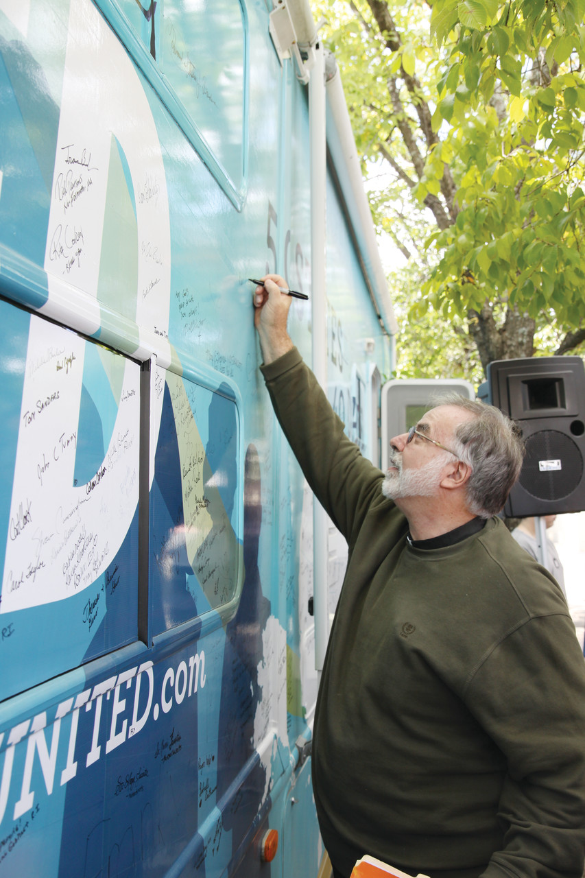 Father Paul Desmarais, pastor at St. Mary's Parish, Carolina, signs the 40 Days for Life United tour bus.