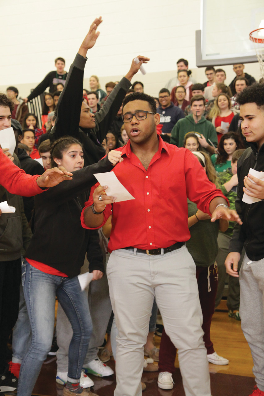 "Senior Joseph Gomes leads his classmates in a boisterous rendition of ""Rudolph the Red-nosed Reindeer"" during the presentation ceremony in the school gym."