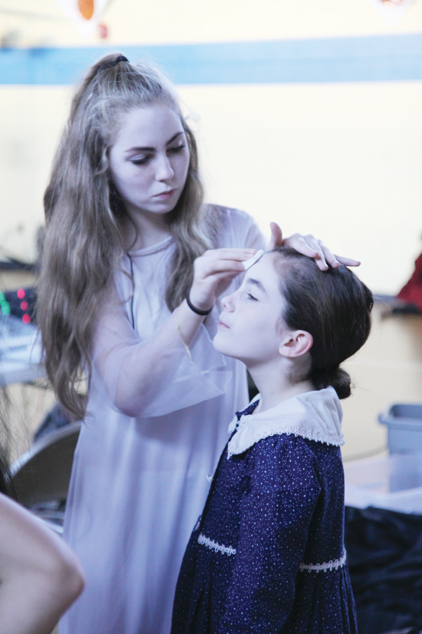 Eighth grader Lily McMahon helps her sister, Mary, with her face paint as the two actresses prepare for the dress rehearsal on Friday afternoon.