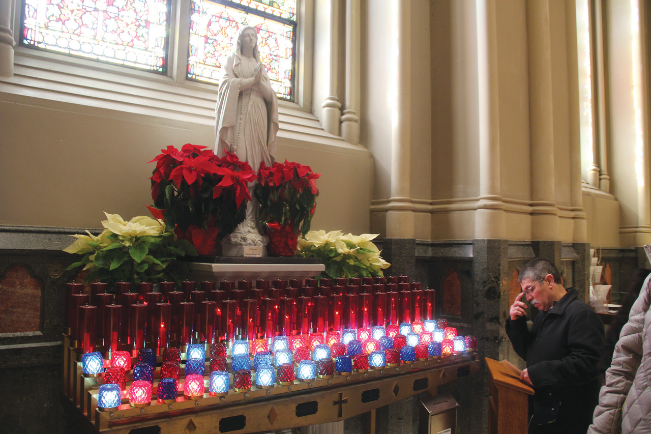 Following the Mass to begin the diocesan Year with Mary Our Mother, a man prays before the statue of the Blessed Mother in a special devotional area created for the faithful to pray during the Marian year at the Cathedral of Saints Peter and Paul, Providence.