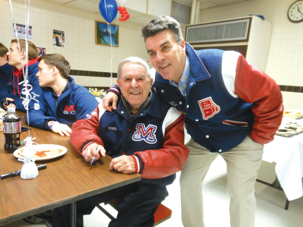 "Normand ""Bill"" Belisle, hockey coach of 42 years at Mount St. Charles Academy, and his son, Dave, smile at an event honoring the older Belisle's induction into the U.S. Hockey Hall of Fame last fall."