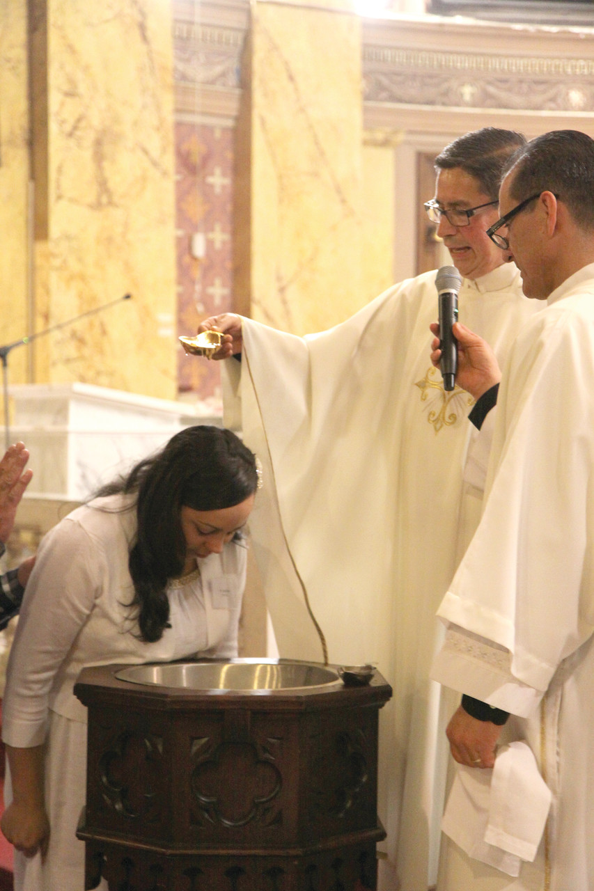 Damaris Navarro receives the sacrament of baptism.