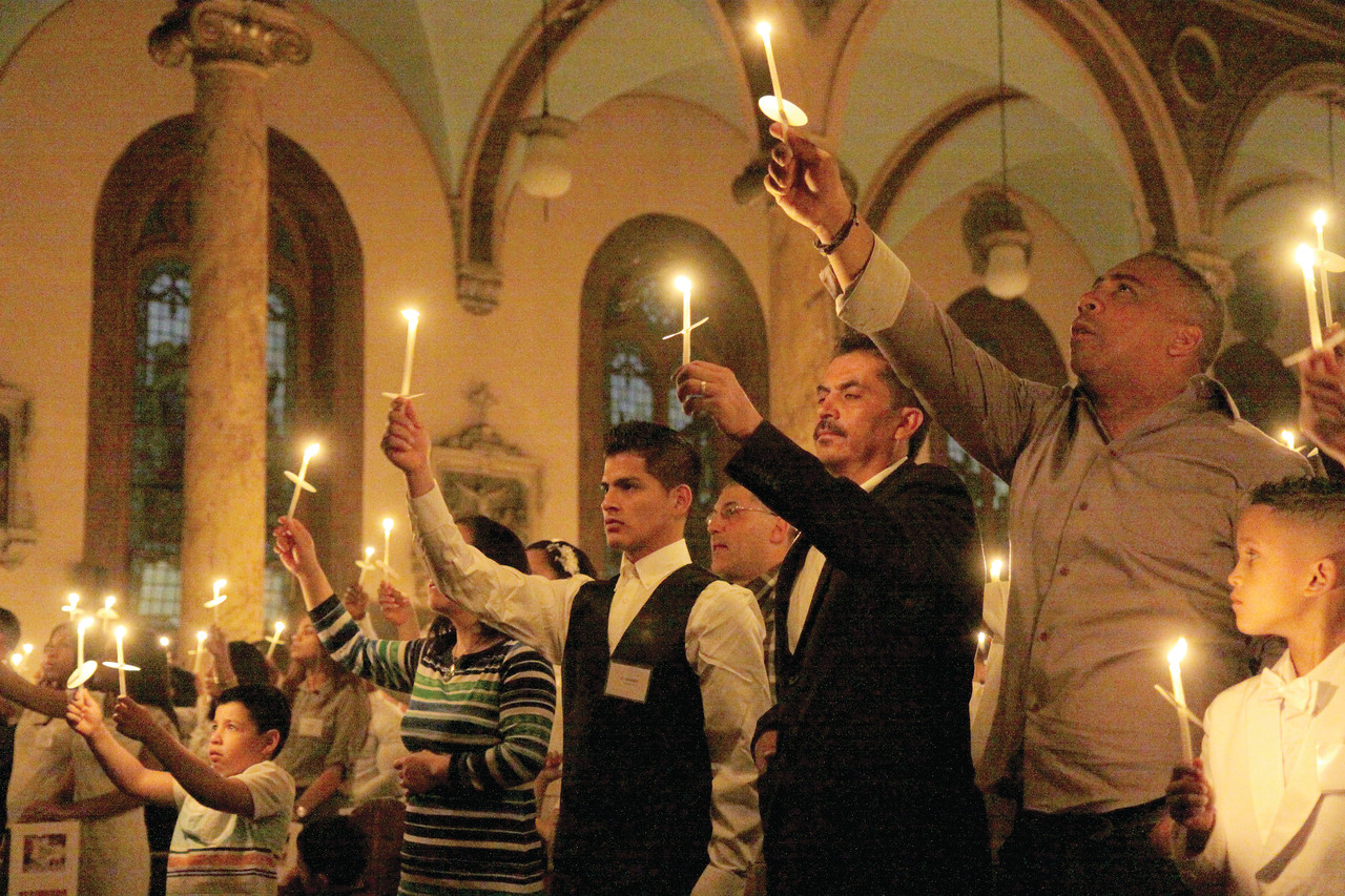 Parishioners at St. Charles Borromeo Parish, Providence, raise their hands in prayer during the candle-lighting at the start of the Easter Vigil.​​​​
