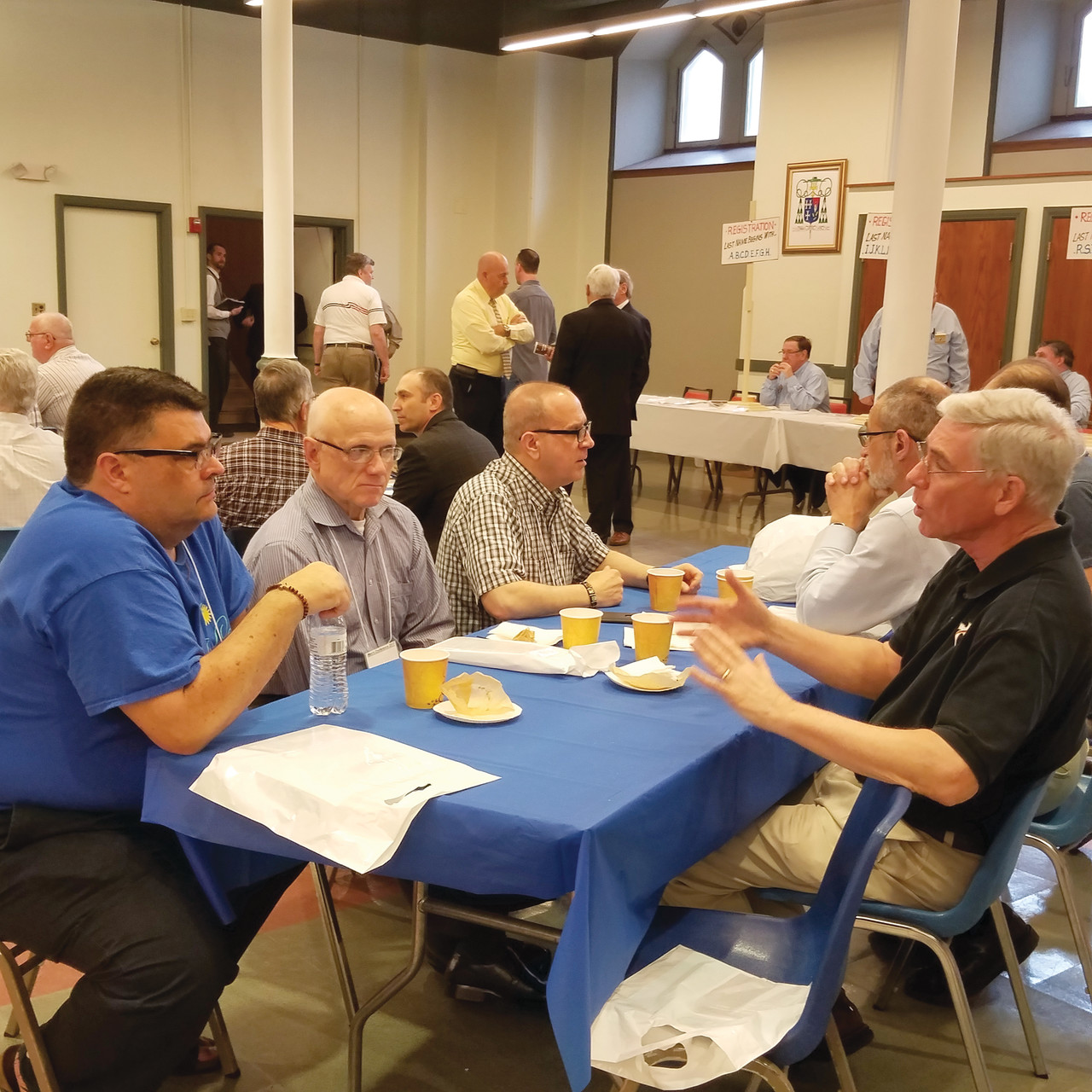 Deacon Noel Edsall, right, confers with fellow participants during a break in the annual Diocesan Men's Conference, held Saturday at the Cathedral of SS. Peter and Paul and the adjacent McVinney Auditorium.