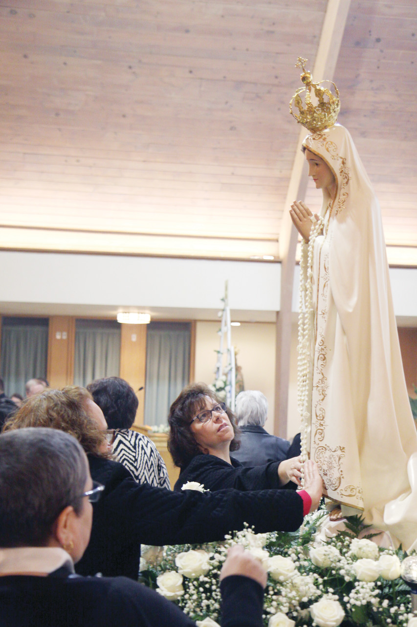 Parishioners and visitors to Our Lady of Fatima Church, Cumberland, venerate a statue of the Blessed Mother following a procession Saturday evening.