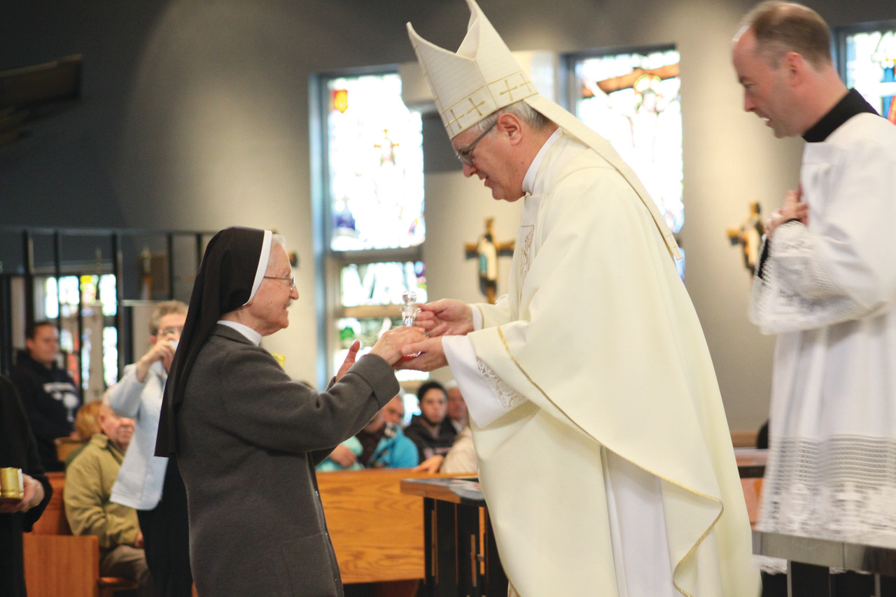 Sister Mary Antoinette, a Daughter of Our Lady of the Garden celebrating 60 years of religious life, offers the wine to Bishop Tobin during Sunday's Mass honoring religious jubilarians.