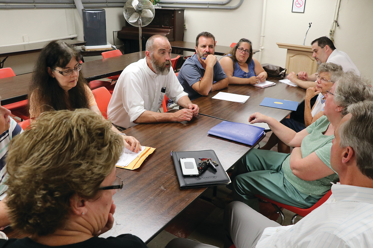Father Daniel J. Sweet, pastor of Our Lady Queen of Martyrs Parish, Woonsocket, meets on July 19 with parishioners who are developing a plan to serve the needs of the local faithful.