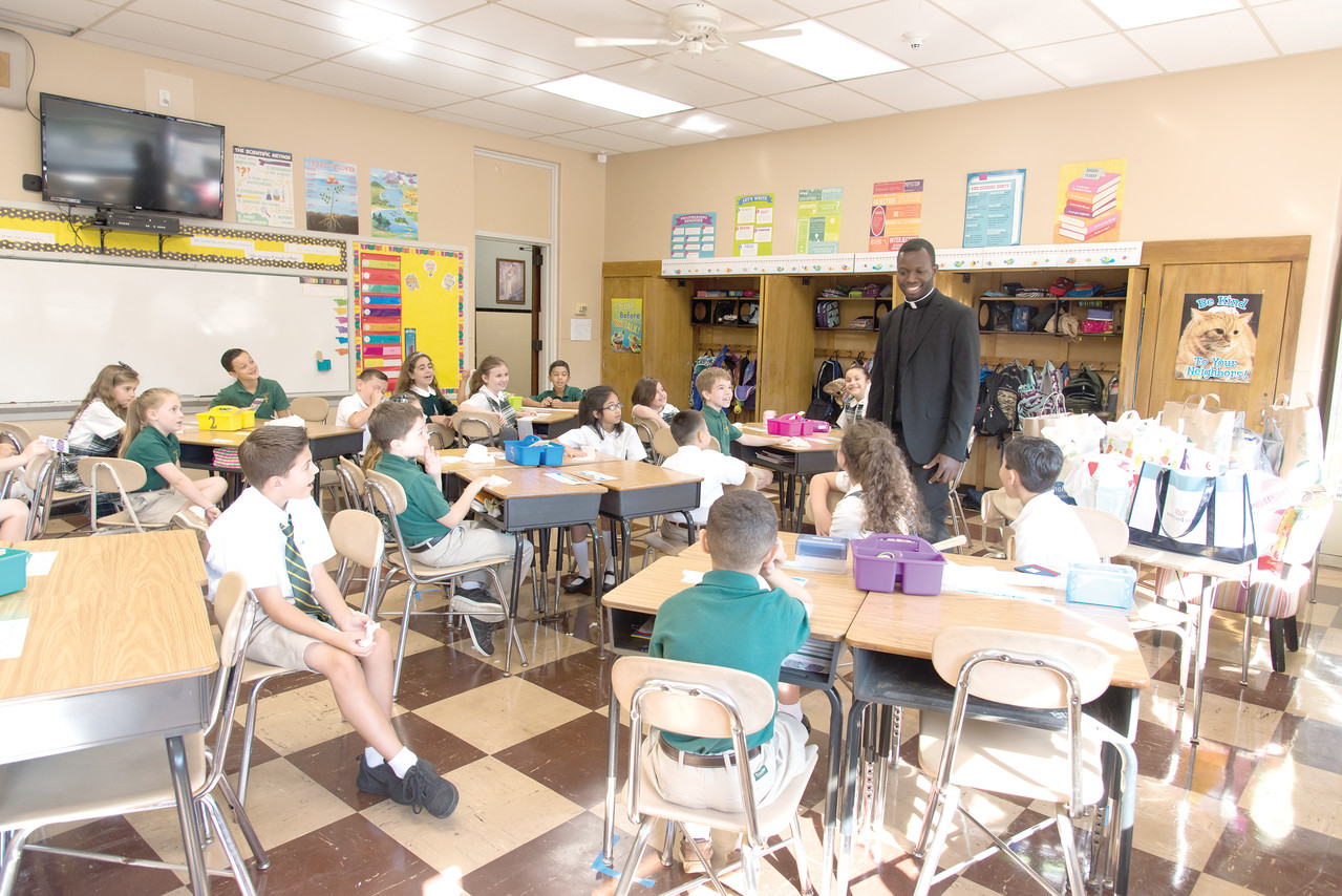 Newly ordained Father Jean Joseph Brice visits the third grade classroom at Saint Augustine School on their first day back to class on August 28. Father Brice is serving as Assistant Pastor of Saint Augustine Parish in Providence.