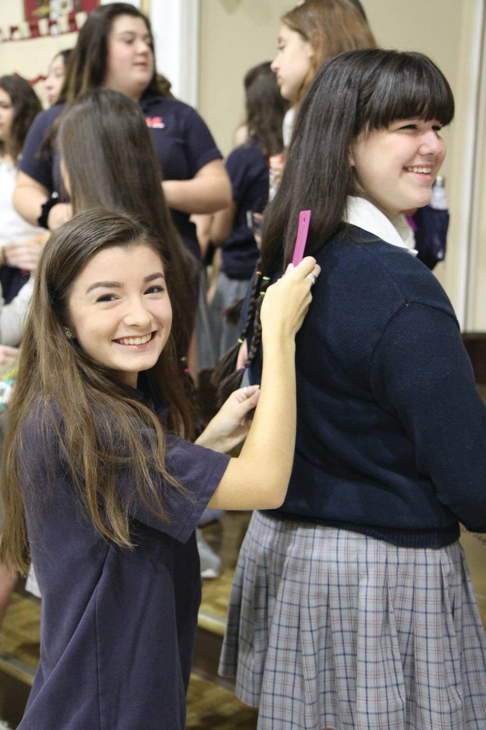 Marissa Kanakry measures fellow student Emma Van Reysen's hair before it is cut for donation.