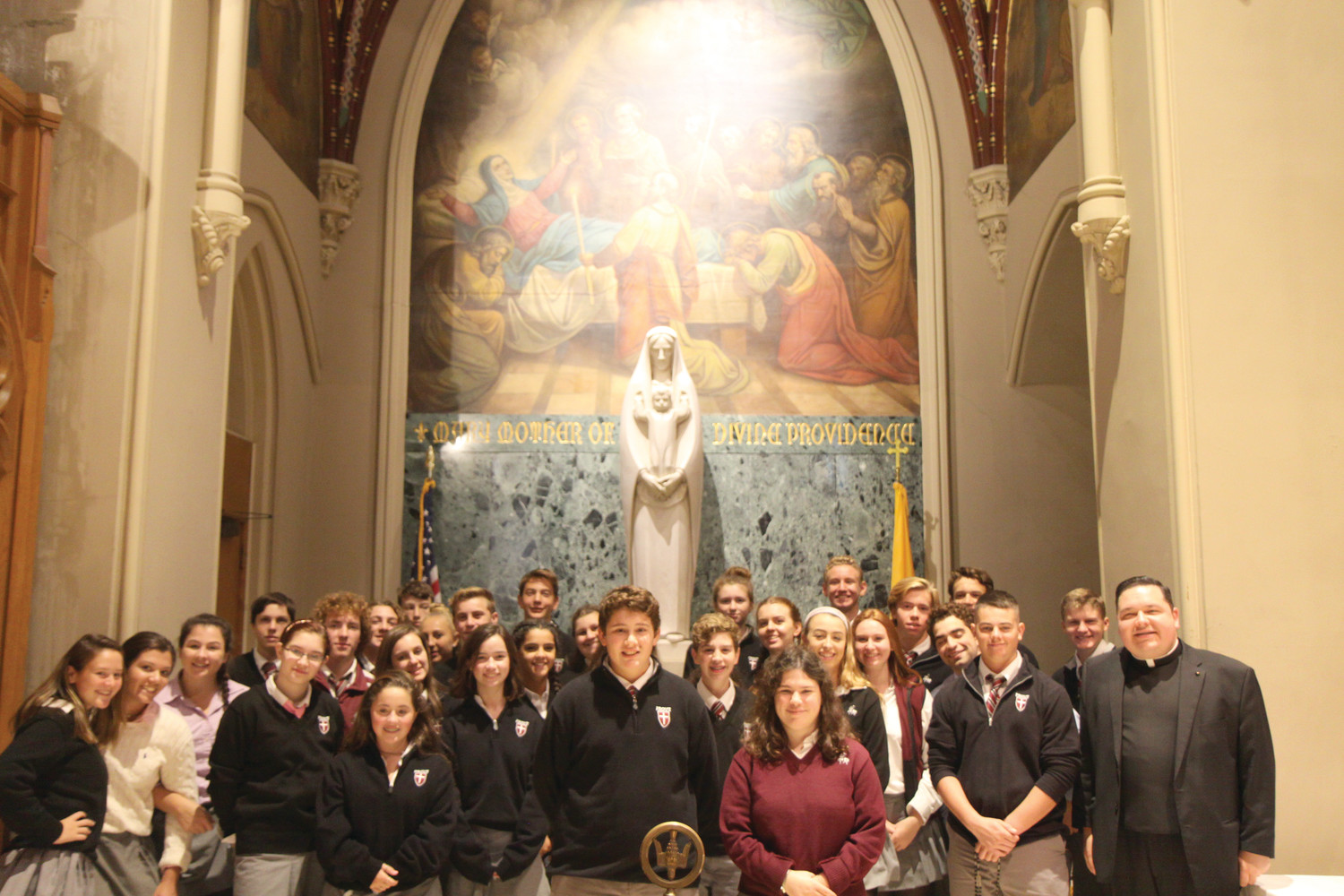 Students, along with Chaplain Father Joseph Upton, pose for a photo before a statue of Our Lady of Providence at the Cathedral of Saints Peter and Paul.