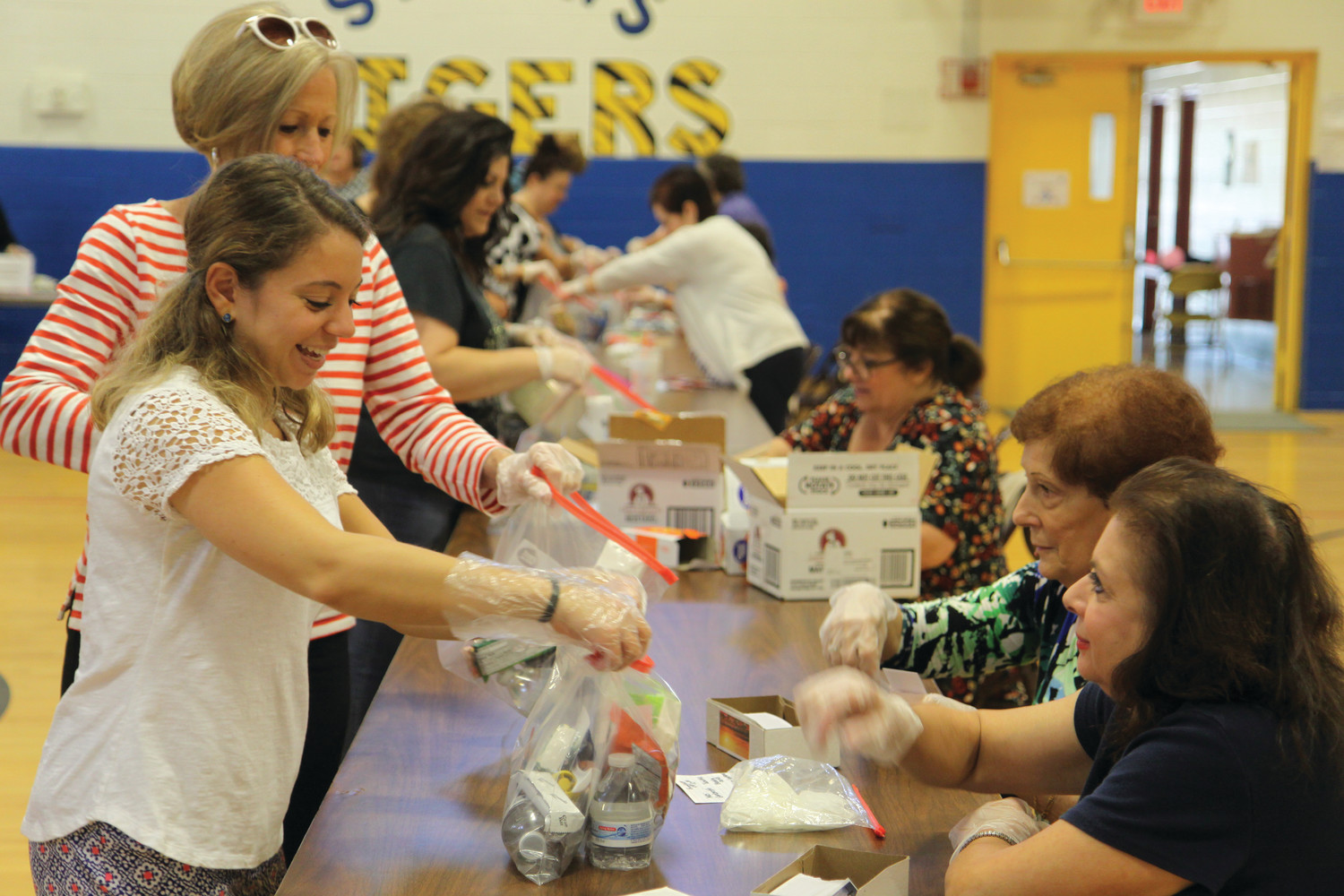 Kaitlyn DiTraglia (left) collects a prayer card for a bag lunch from fellow volunteers during a service project at St. Mary Parish Center, Cranston, on Sunday, September 24.