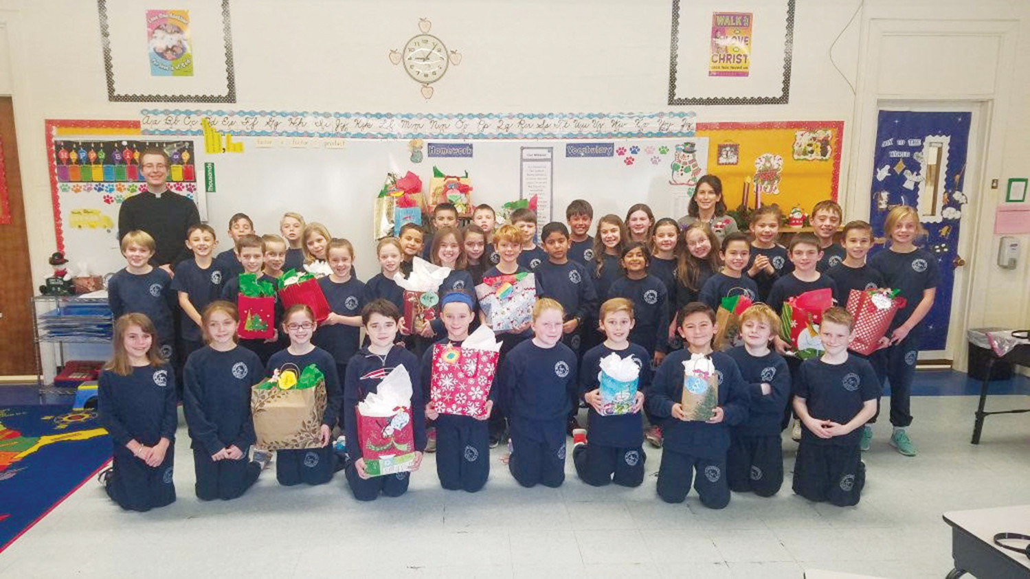 Rhird-graders gather with Associate Pastor Father Joshua Barrow and Teacher Jill Hackett with a collection of Christmas presents for the residents. Jeanne Perretta is missing from the photo.
