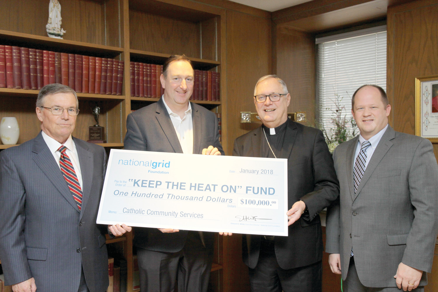 "From left, Michael Ryan, director of government affairs for National Grid Rhode Island, and Ed White, executive director of the National Grid Foundation, present Bishop Thomas J. Tobin and James Jahnz, emergency assistance network coordinator for the diocese, with a $100,000 donation to the ""Keep the Heat On"" program."