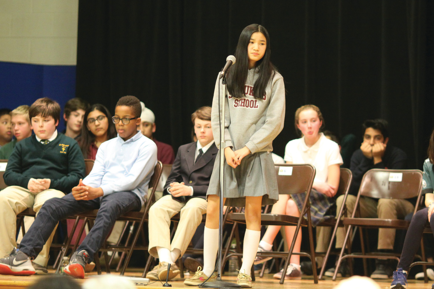 Mary Rose Comerford, an eighth grader representing St. Luke School, Barrington, waits for her word as other students nervously prepare for the second round.