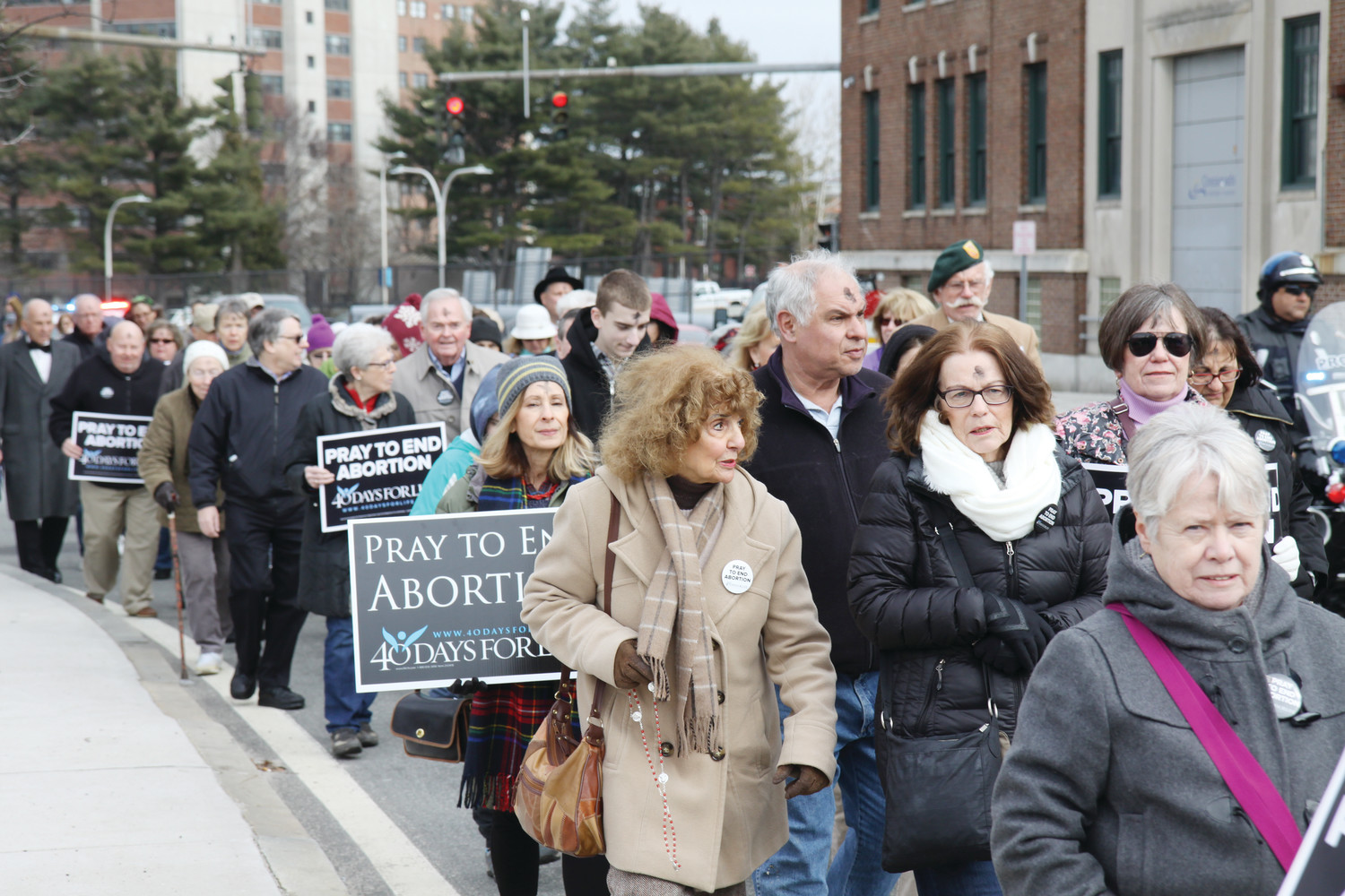 A large group of pro-life advocates, led by Bishop Thomas J. Tobin and accompanied by a police escort, marched to the Providence Planned Parenthood clinic following Ash Wednesday Mass on February 14. The procession marked the start of the 40 Days for Life Lenten prayer campaign.