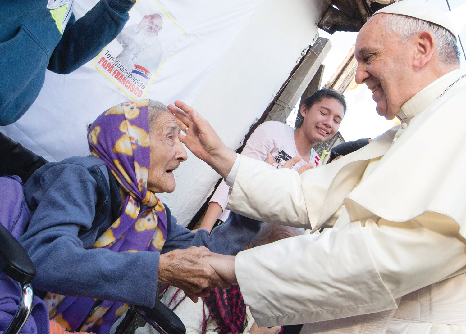 Pope Francis greets an elderly woman as he meets with people of the Banado Norte neighborhood in Asuncion, Paraguay, in this July 12, 2015, file photo. The pope has shown special concern for the aged, the sick and those with disabilities.