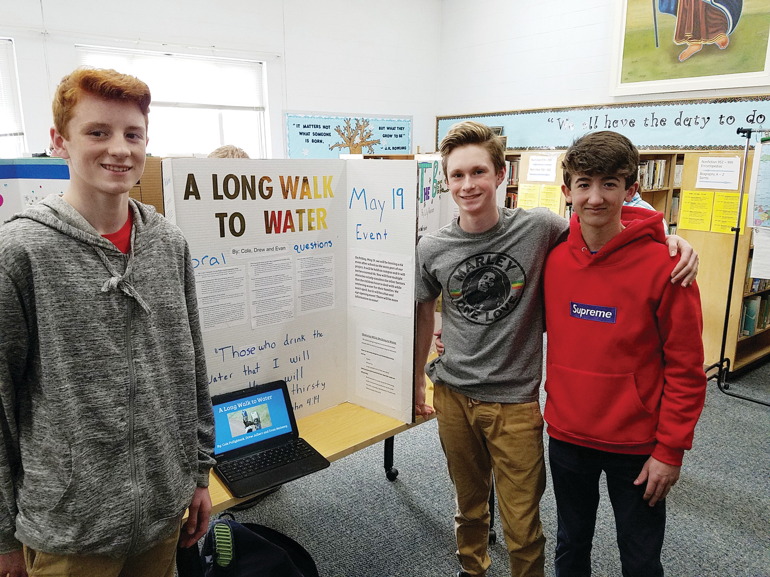"Pictured are Evan Maloney, Cole Pullyblank and Drew Jalbert presenting their project ""A long walk to water."""