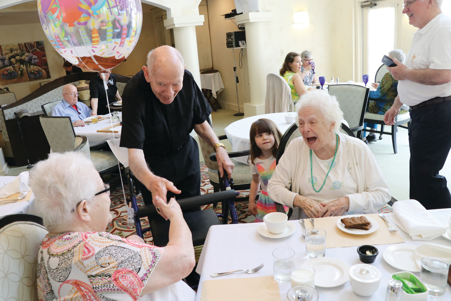 Bishop Emeritus Louis E. Gelineau visits with residents of The Villa at Saint Antoine on his 90th birthday, May 3.