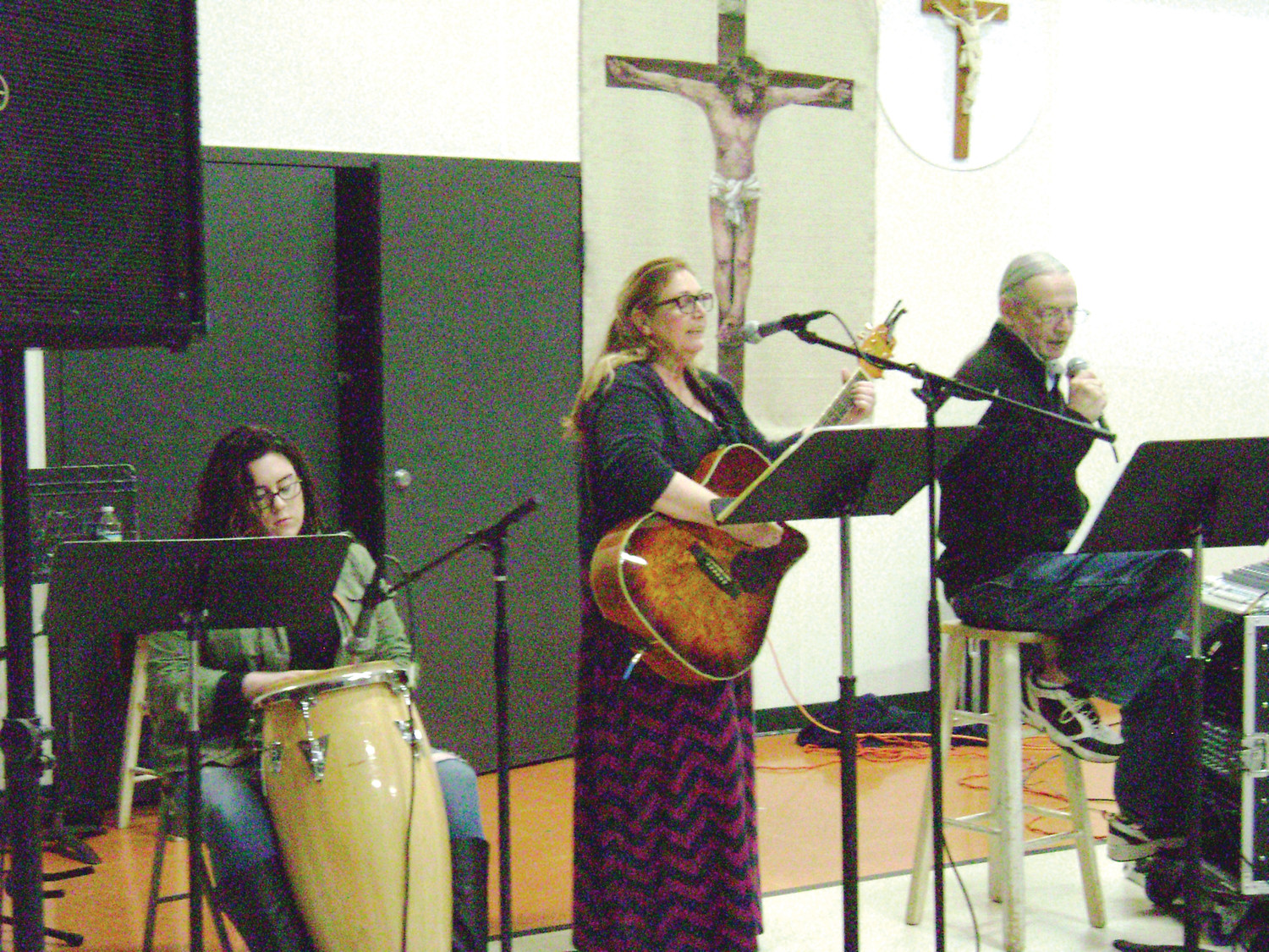 From left, praise and worship team Sarah Mulholland, Mary McDonough and Bob Finnegan lead the Charismatic prayer group in song at St. Patrick's Church on Thursday, April 19.