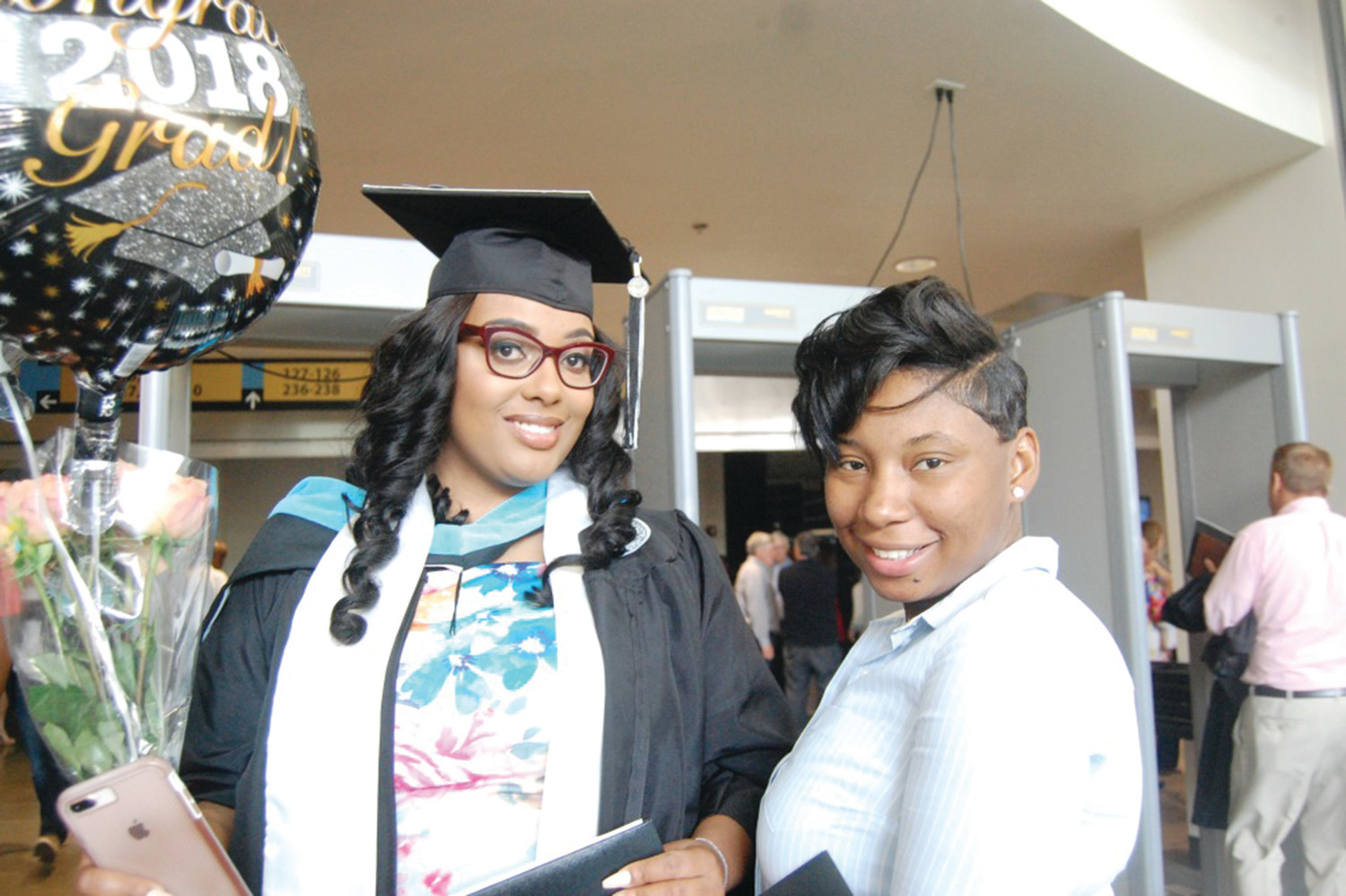 Quameé Andrade, left, who received her Master's in Education, smiles with her sister Denise Geegbae following her graduation from Providence College.