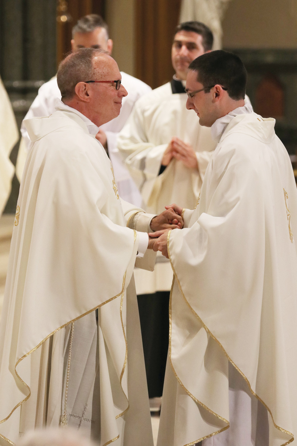 Father Henry Zinno, a mentor to Father Dufour as pastor of his parish of Our Lady of Mount Carmel in Bristol, congratulates the new priest after vesting him.