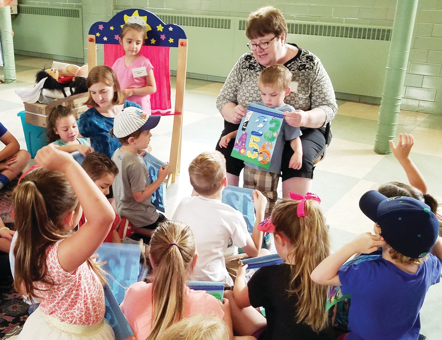 Christine Magowan, director of Faith Formation and Evangelization at St. Pius X Parish in Westerly, planned a successful five-day morning Vacation Bible School program for about 25 of the parish's children. Above Magowan talks to the children about the creation story.