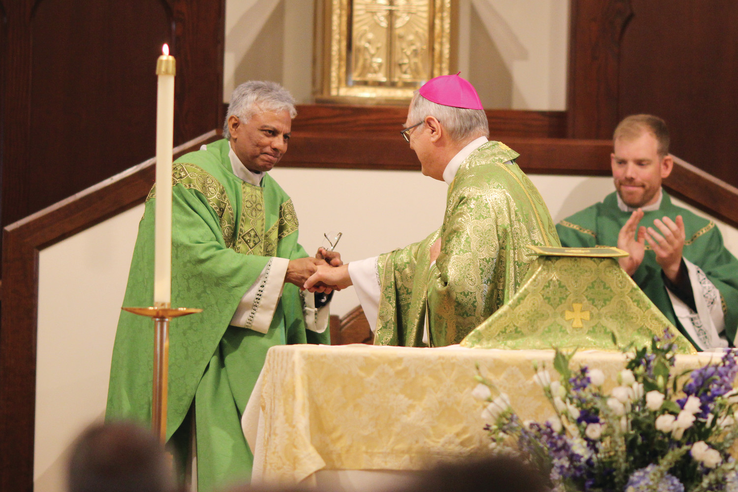 Bishop Tobin and Father Brian Morris, associate pastor, congratulate Father Varghese.