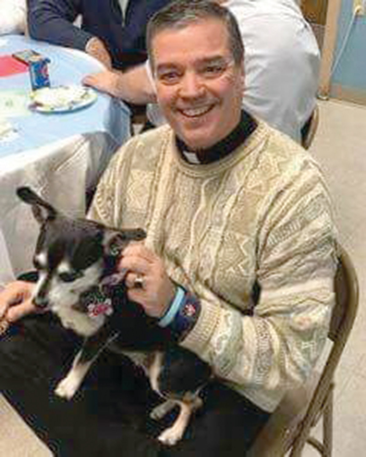 Father John Soares, the pastor at St. Thomas Church in Providence, smiles with his dog Dusty Rose. Father Soares has served St. Thomas Church and it's school community for the past 11 years.