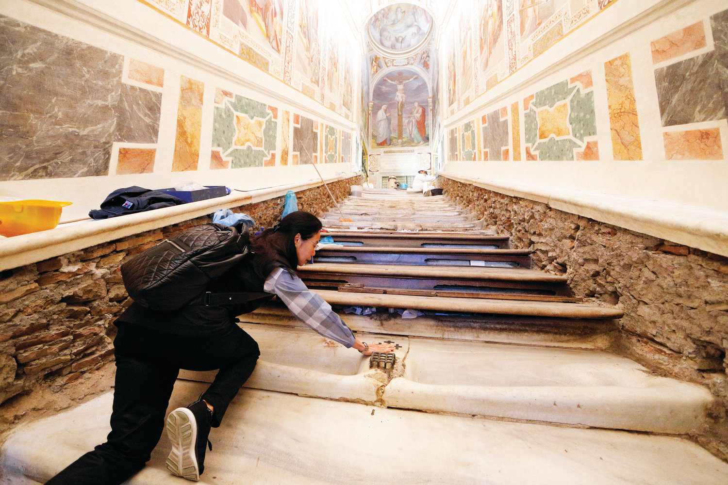 Mei Wen of Perth, Australia, touches an area of the Holy Stairs where Jesus is believed to have fallen, during restoration work at the Pontifical Sanctuary of the Holy Stairs in Rome March 15, 2019. Wen is one of the major donors who contributed to the restoration of the sanctuary. Pilgrims will have the opportunity to climb the bare marble stairs for at least a month after an April 11 unveiling of the renovated sanctuary.