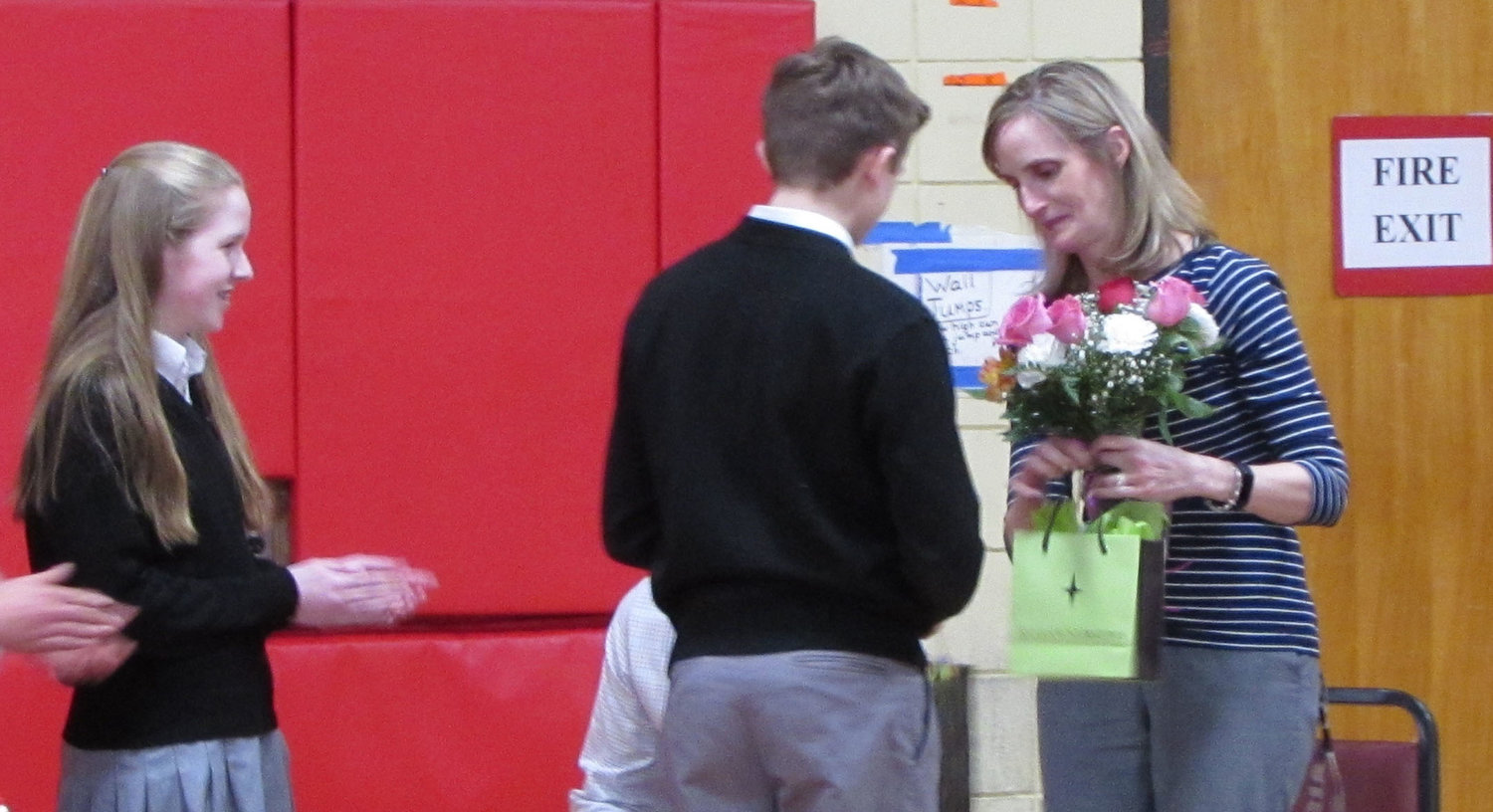 Eighth graders Anna Vredenburg and Ryan Stone present Principal Senenko with gifts and flowers from the school.