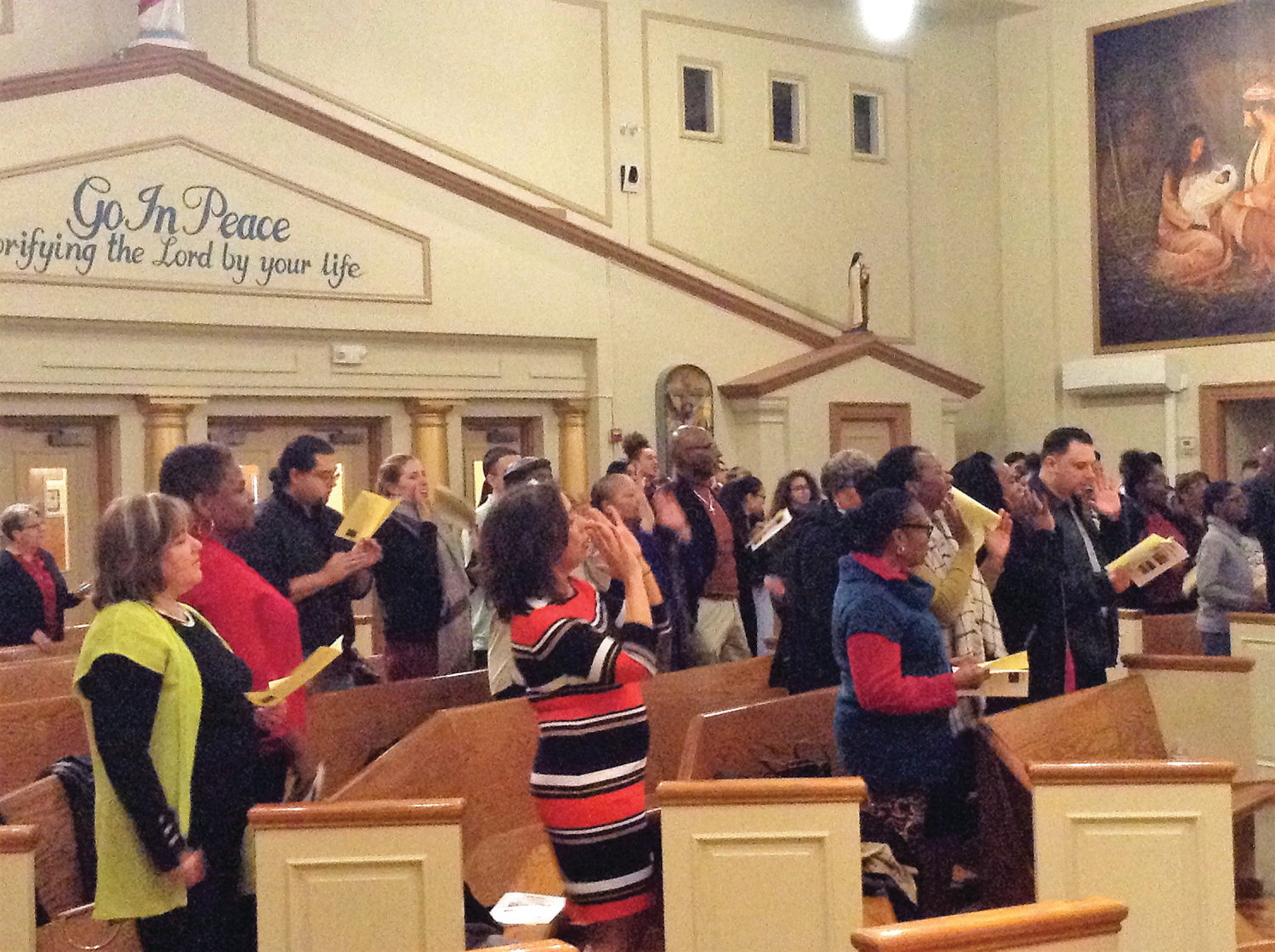 "The crowd at the recent Black History Month celebration at St. Patrick Church, Providence, performs a simple dance together while singing ""Ain't Gonna Let Nobody Turn Me Around.""  The celebration was originally scheduled for February 12, but inclement weather forced a postponement."