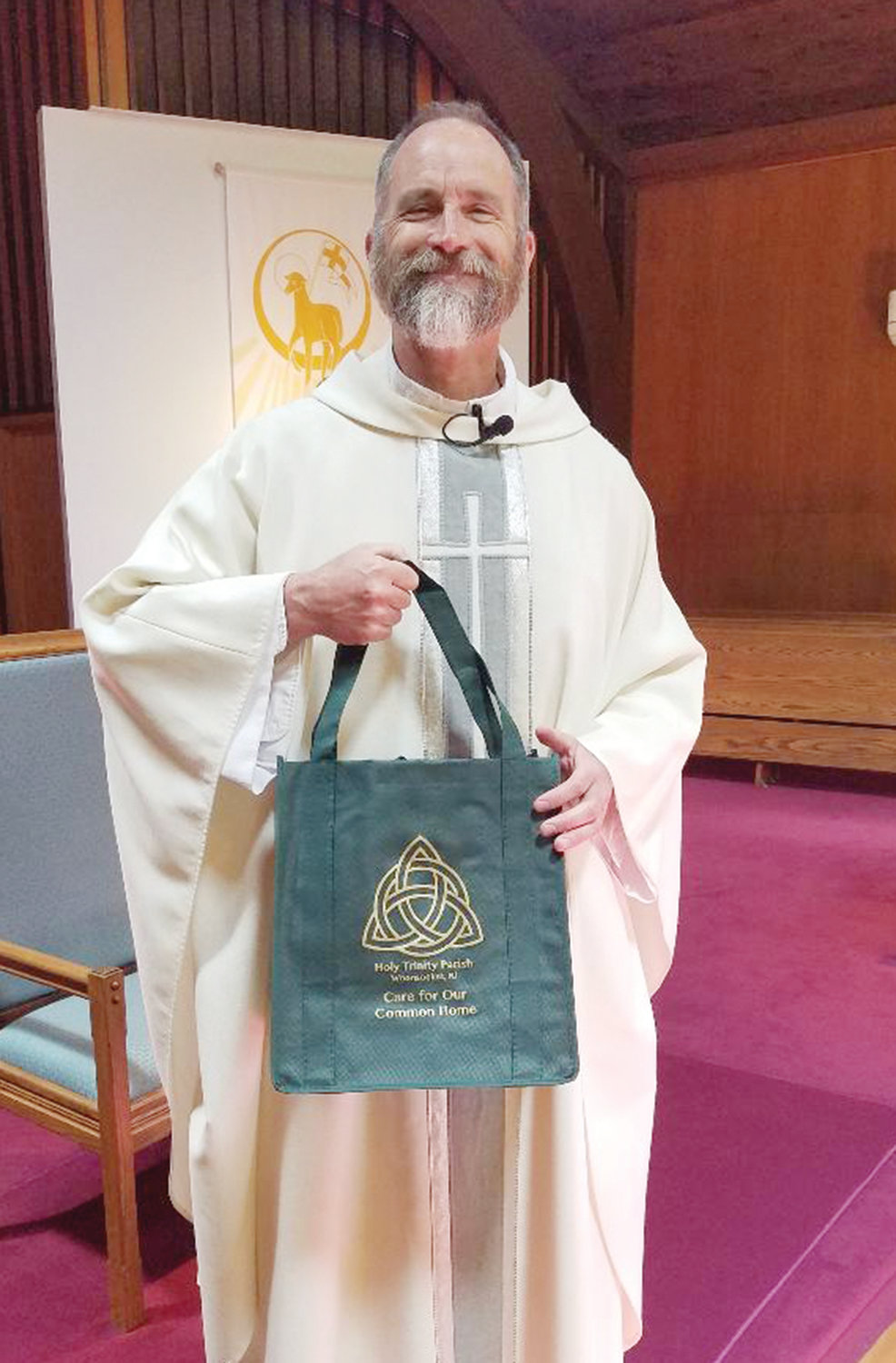 "Father Daniel J. Sweet, pastor of Holy Trinity Parish, holds one of the reusable mesh shopping bags designed and purchased by the parish's Social Justice Committee to promote unity among the newly converged faithful from the three different churches and to express their shared commitment to be good stewards of the Earth. Adorned with the parish's Trinitarian logo, the bags also serve as tools of evangelization, even when the parishioners are grocery shopping. ""In our work for social justice and evangelization we can take small but powerful steps to address the needs of our human family,"" said parishioner Rob Robbio."