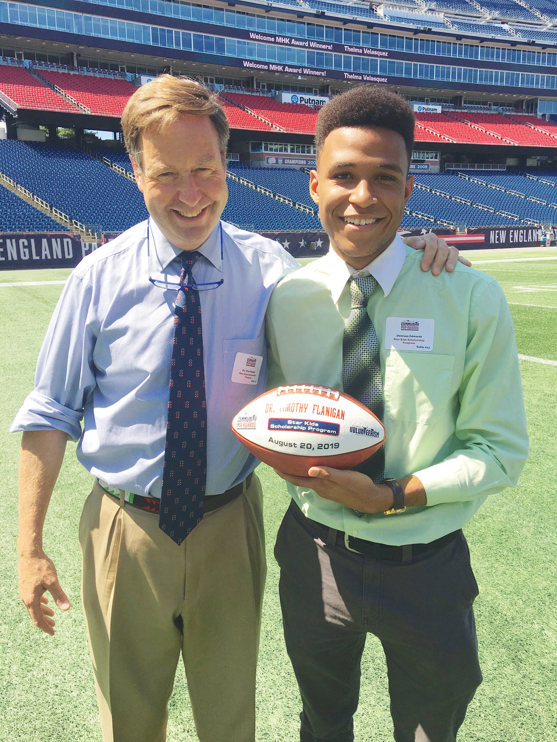 Deacon Dr. Flanigan shares his 2019 Myra Kraft Community MVP Award on the field at Gillette Stadium with Star Kid Duwuan Edwards, of Newport.