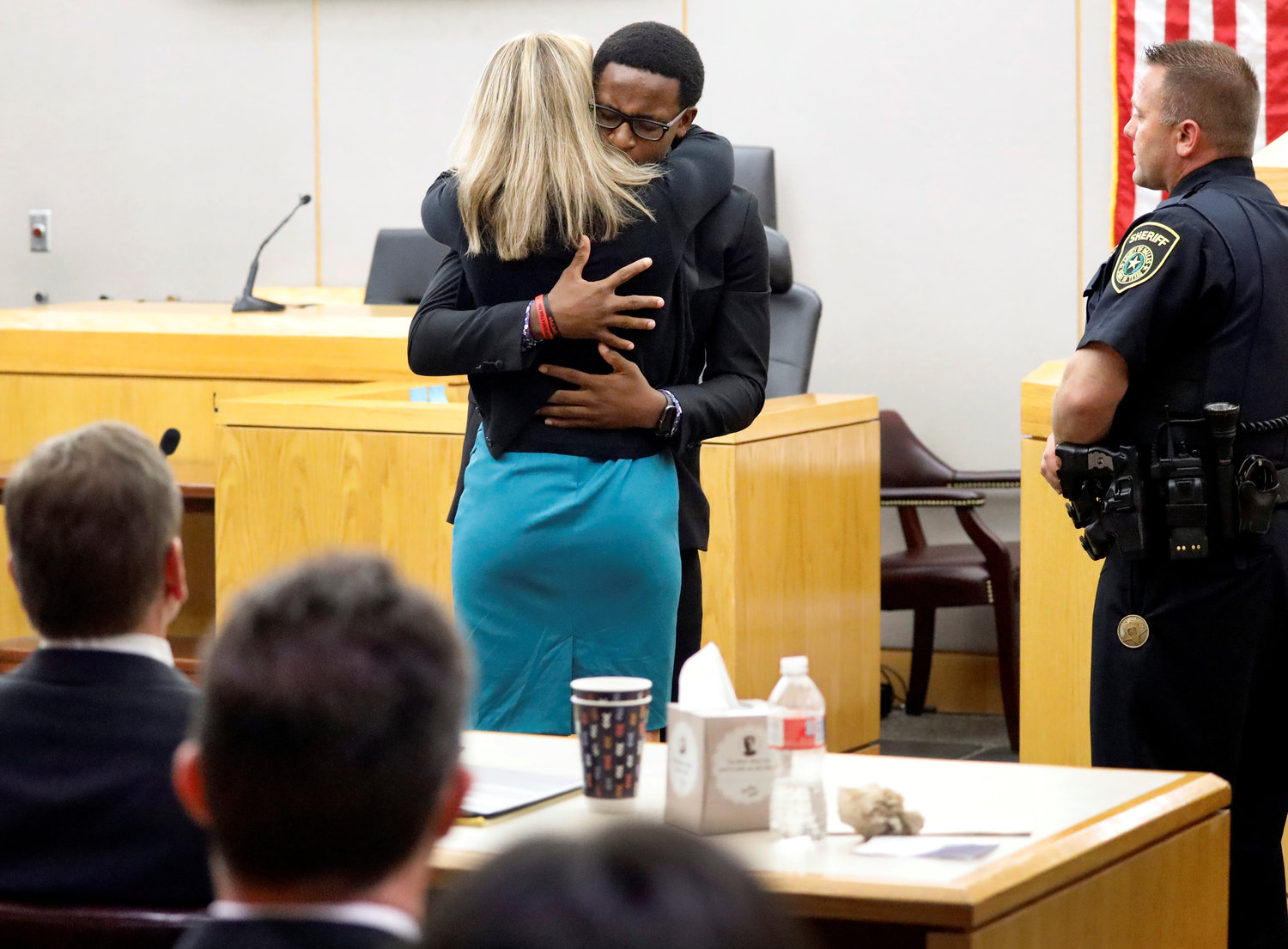 Brandt Jean, the younger brother of murder victim Botham Jean, hugs former Dallas police officer Amber Guyger after delivering his impact statement to Guyger at the Frank Crowley Courts Building in Dallas following her Oct. 2, 2019, sentencing to 10 years in prison for murdering Botham. (CNS photo/Tom Fox pool via Reuters) See DALLAS-BISHOP-FORGIVENESS Oct. 3, 2019.