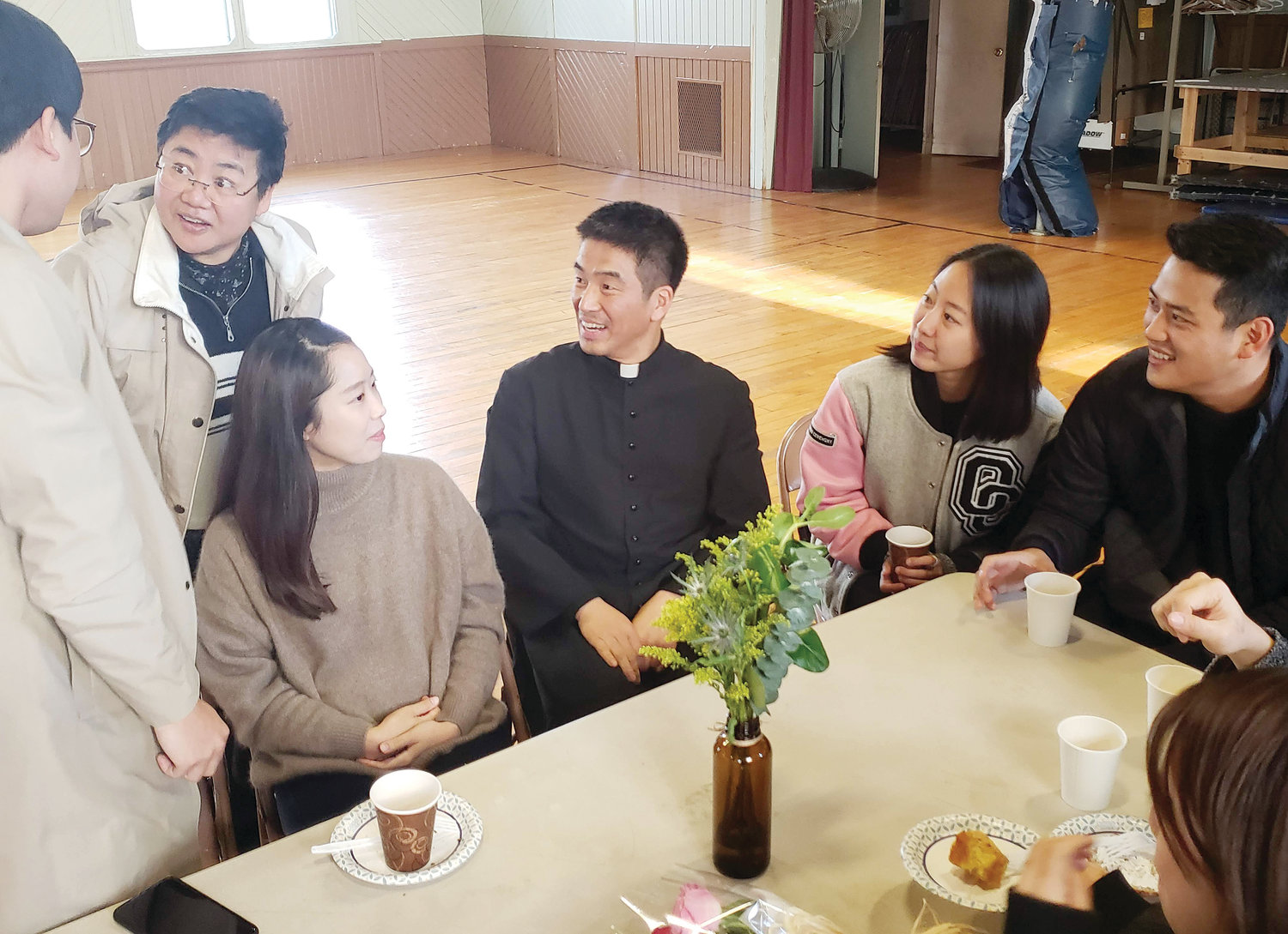 Father Jaekyu Lee, Chaplain to Rhode Island's Catholic Korean community and assistant pastor at St. Paul Church in Cranston, visits with Korean faithful after Mass.