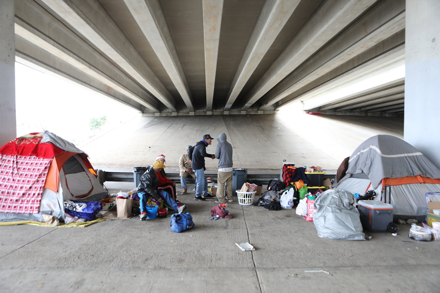 Homeless men are seen under a bridge on Christmas day in Austin, Texas. Catholic Charities staff are warning that the coronavirus pandemic presents a stark threat to the U.S. homeless population.