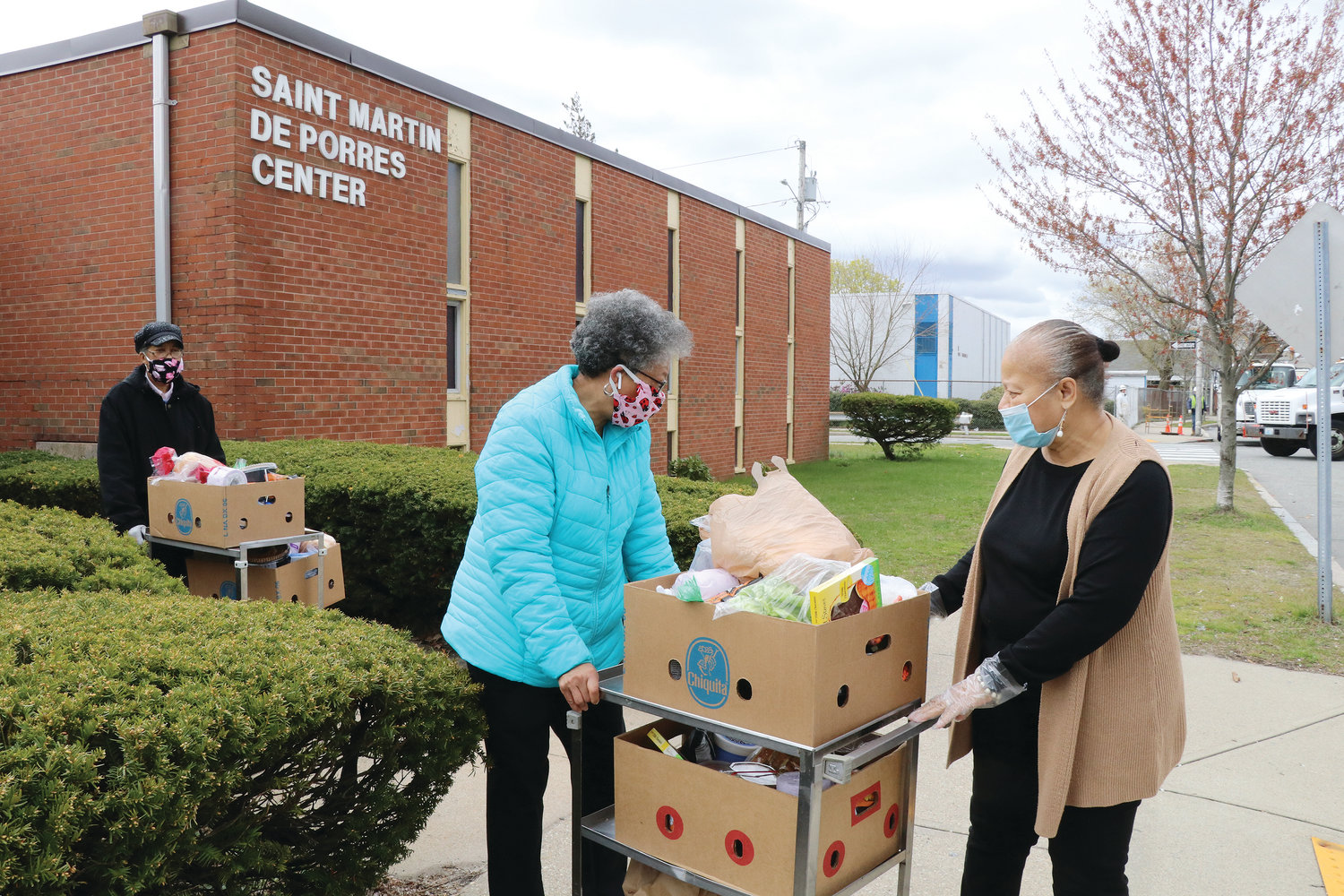Director Linda A'Vant-Deishinni, at right, helps volunteers Cheryl Gray, left, and Gail Harris move boxes of food to their vehicle for distribution to homebound seniors in need.