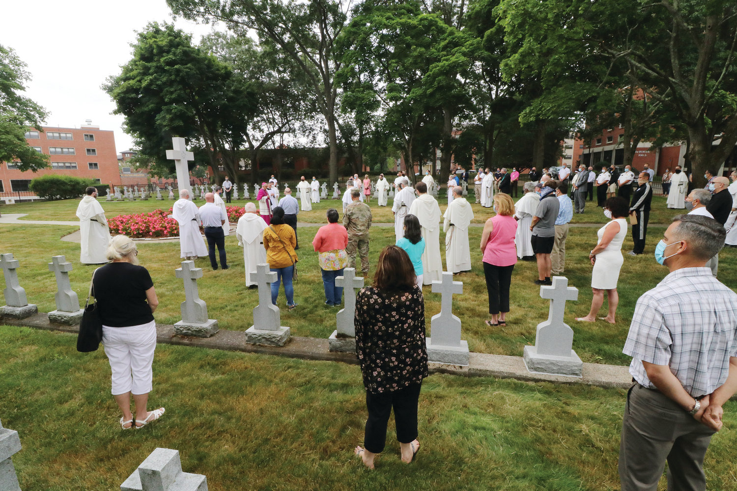 About 75 friars and members of the Providence College community gathered for the solemn ceremony during which Bishop Thomas J. Tobin blessed the grounds with holy water and incense — including the large granite crucifix standing in a garden of flowers at the center of the cemetery — as he offered prayers of consecration.