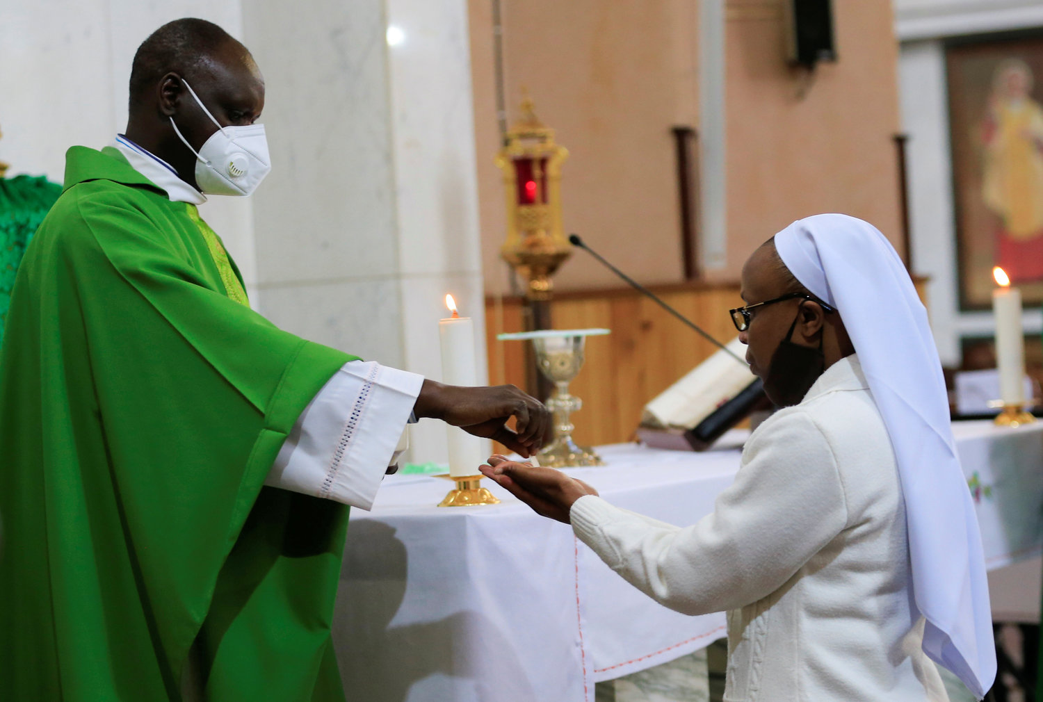 A priest wearing a face mask gives Communion to a woman religious during a July 19, 2020, Mass at the Cathedral Basilica of the Holy Family in Nairobi, Kenya, on the first day the government allowed churches to reopen for worship during the coronavirus pandemic. The Vatican issued a new instruction July 20 on pastoral care that emphasizes the role of lay men and women in the church's mission, but said most parishes must be led by priests.