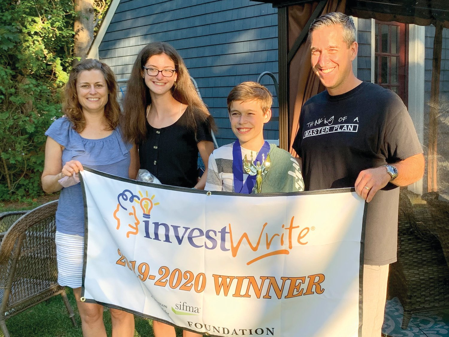 Evan Gendreau of Seekonk, Mass., smiles with his parents, Michael and Melanie, and sister Kelsey. The family was surprised at their home by Gendreau's teacher Laura Doliber and St. Margaret School Principal Lee Ann Nunes, who informed Evan that he had won the National InvestWrite® Competition.