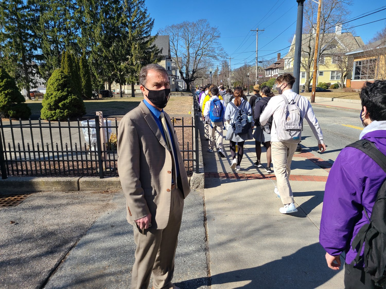 St. Raphael Principal Daniel Richard greets students as they walk outside on their way to class.