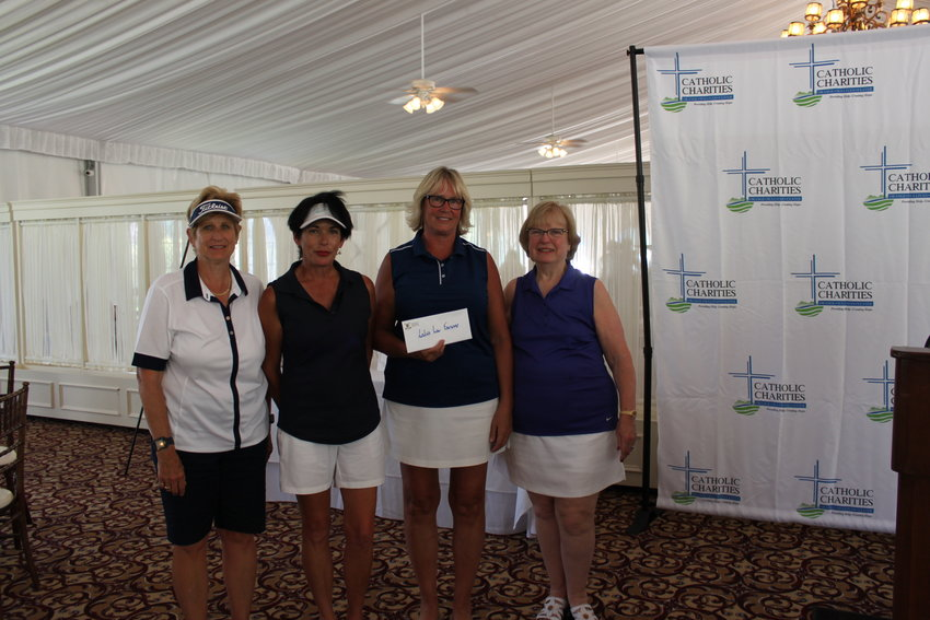 Lori Ransom, Jeannie Tomita, Denise Freeman, and Mary Bonura show off the envelope with their prize for winning first place in the women's foursome at the Catholic Charities Golf for Charity outing.