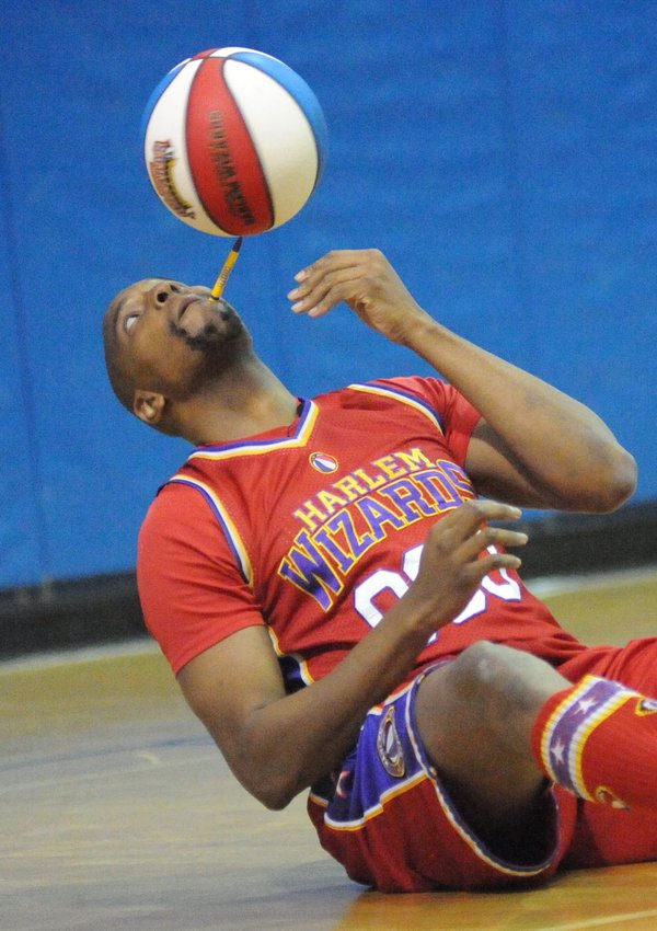 """A delicate balance. The Wizards' Dwayne """"Swoop"""" Simpson balances a basketball on his chin using a ballpoint pen."""