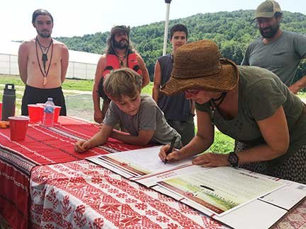 Tannis Kowalchuk signs the Friendship Treaty being carried by the Lenape and supporters down the Delaware River.