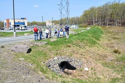 """TRR photos by Sandy Long    The Pike County Training Center features several stormwater best management practices (BMPs). The vegetated diversion berm at right in this photo conveys runoff around the site rather than through it, minimizing erosion of soils and the amount of stormwater that needs to be managed on site. Other features include a wetland forebay and wet pond, which receive runoff from impervious surfaces, as well as infiltration berms, which trap pockets of water, allowing it to soak into the ground. The various elements are all part of the site's """"treatment train"""" of stormwater BMPs."""